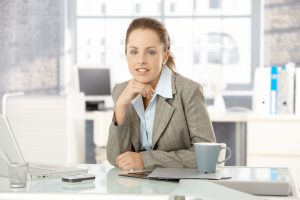 Young attractive businesswoman sitting by desk in office, having laptop.